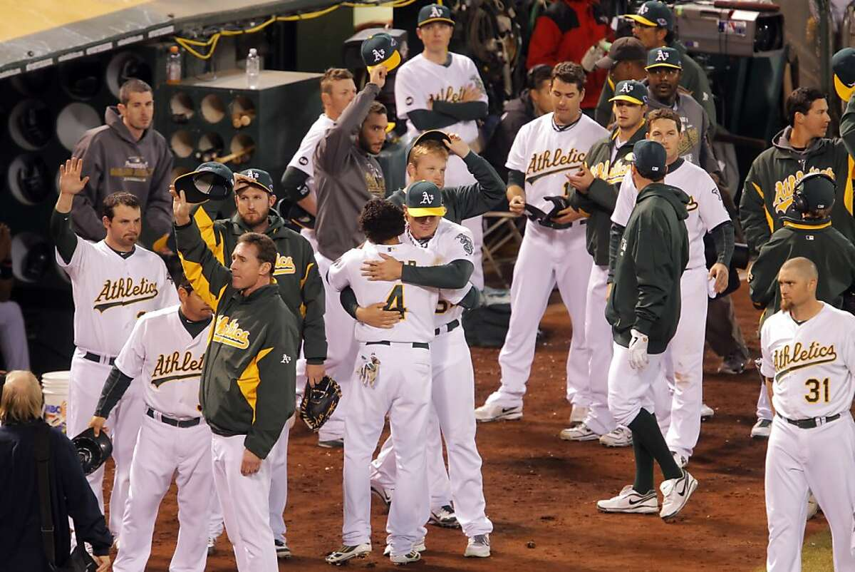 The A's players embrace and raise their hats to the fans as the Tigers celebrate on the field after they lost to the Tigers 6-0. The Oakland Athletics lost 6-0 to the Detroit Tigers in game 5 of the ALDS at O.co Coliseum in Oakland, Calif. on Thursday, October 11, 2012.