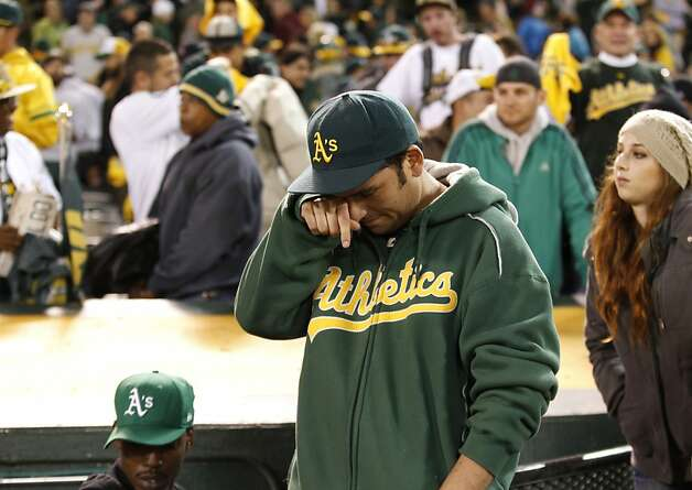 "Leis Portilla of Napa wipes a tear after the A's lose to the Detroit Tigers. The A's Adam Rosales gave Portilla a bat after Portilla told him in Spanish, ""Thank you for a great year."" Photo: Beck Diefenbach, Special To The Chronicle"
