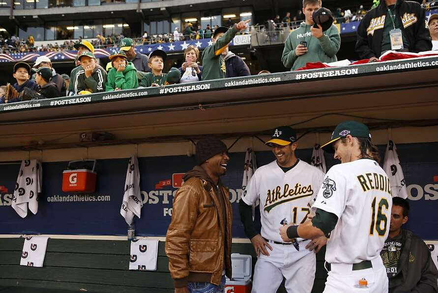 Josh Reddick, right, and Adam Rosales, center, laugh with MC Hammer, left, in the dugout before Hamm