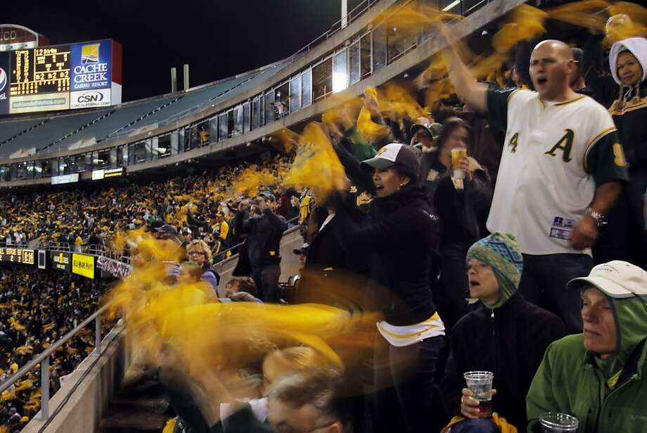 Fans in the upper deck wave their rally towels urging on the A's as they play the Tigers. The Oakland Athletics played the Detroit Tigers in game 5 of the ALDS at O.co Coliseum in Oakland, Calif. on Thursday, October 11, 2012. Photo: Carlos Avila Gonzalez, The Chronicle
