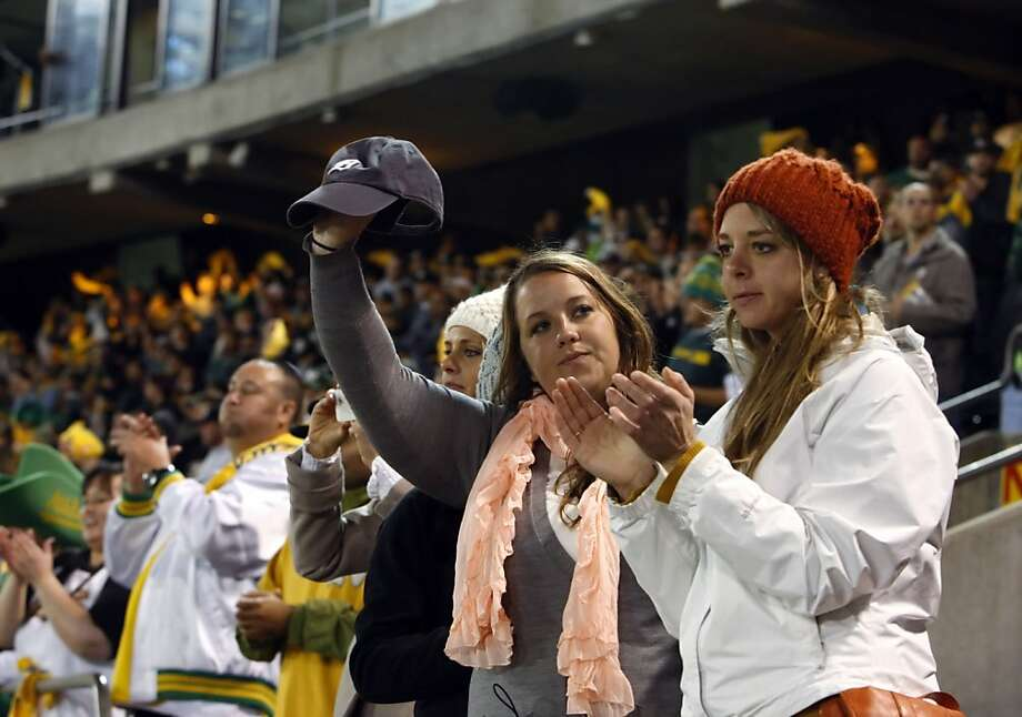 Carla Dodde, right, and her cousin Stephanie Dodde, left, salute the A's after they lost to the Tigers and tipped their caps to the fans. The Oakland Athletics lost 6-0 to the Detroit Tigers in game 5 of the ALDS at O.co Coliseum in Oakland, Calif. on Thursday, October 11, 2012. Photo: Carlos Avila Gonzalez, The Chronicle