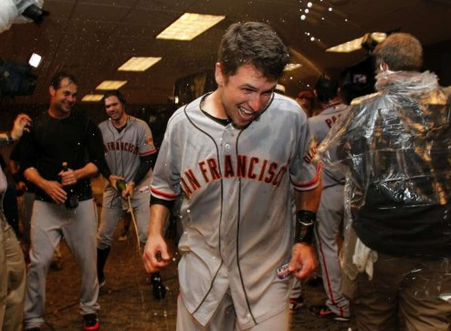 Giants' Buster Posey escapes a spray of champagne as the team celebrates in the clubhouse, as the San Francisco Giants beat the Cincinnati Reds 6-4 in game five to win the National League Division Series in Cincinnati, Ohio on Thursday Oct. 11, 2012. (Michael Macor / The Chronicle)
