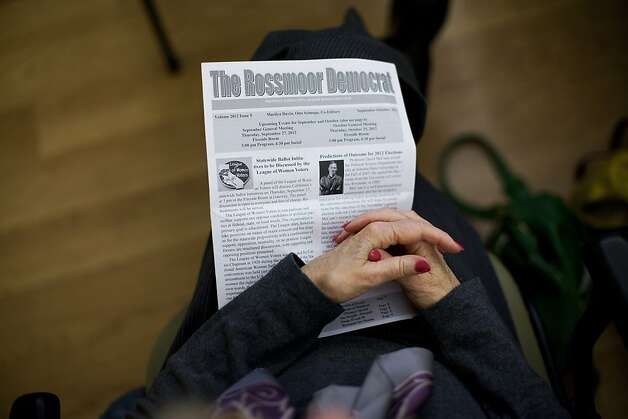 A woman holds a Rossmoor Democrat bulletin as other members of the Rossmoor Democratic Club watch the Vice Presidential debate at the Creekside Country Club in Rossmoor, Calif., Thursday, October 11, 2012. Photo: Jason Henry, Special To The Chronicle