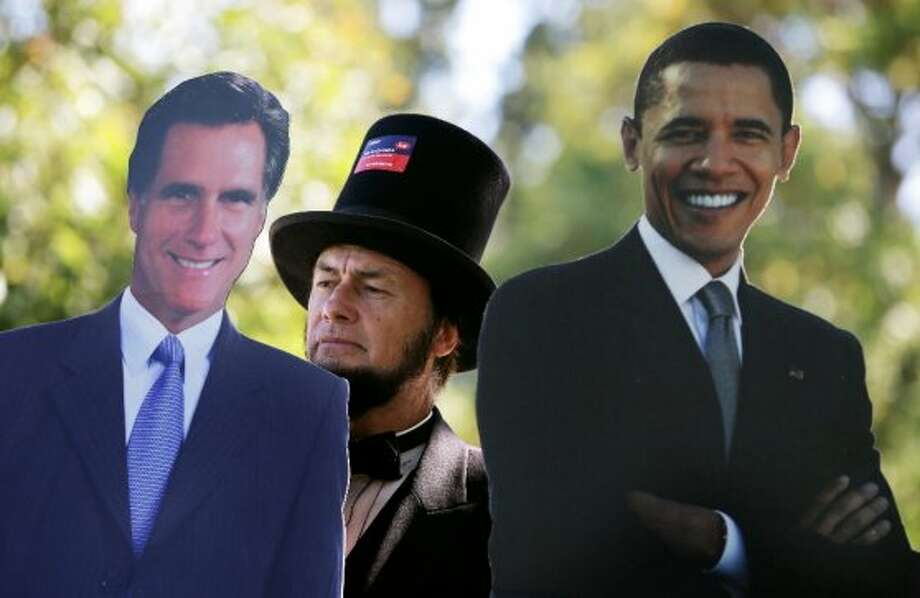 Abraham Lincoln impersonator Larry Elliott, of Louisville, Kentucky, poses with cutouts of Republican presidential candidate Mitt Romney, left, and President Barack Obama outside the Norton Center on the Centre College campus before the vice presidential debate, Thursday, Oct. 11, 2012, in Danville, Kentucky. Vice President Joe Biden will face Republican vice presidential candidate, Rep. Paul Ryan, R-Wis., in Thursday's debate. (AP Photo/Charlie Neibergall) (ASSOCIATED PRESS)