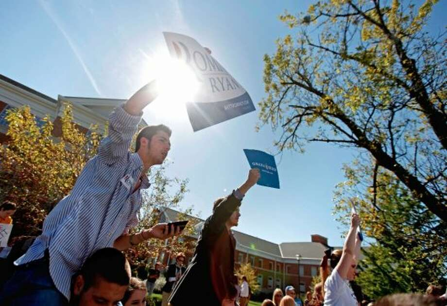Ashton Arvin, 17, left, and John Thompson, 18, right, hold up signs for their respective candidates ahead of the vice presidential debate between Republican vice presidential candidate, Rep. Paul Ryan, R-Wis., and Vice President Joe Biden, Thursday, Oct. 11, 2012, at Centre College in Danville, Ky. (AP Photo/David Goldman) (ASSOCIATED PRESS)
