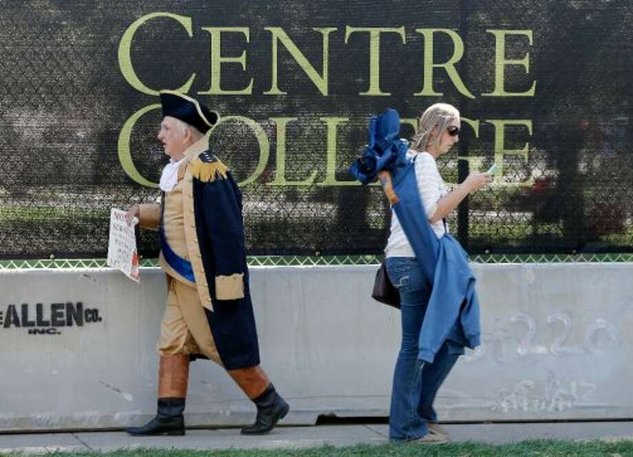 Paul Johnson, dressed as George Washington, left, walks past a barricade at Centre College, site of the vice presidential debate, Thursday, Oct. 11, 2012, in Danville, Ky. Vice President Joe Biden will face Republican vice presidential candidate, Rep. Paul Ryan, R-Wis., Thursday night. (AP Photo/Mark Humphrey) (ASSOCIATED PRESS)