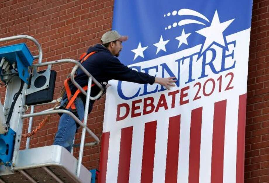 Centre College carpenter Damon Denney hangs a sign outside the Norton Center in preparation for Thursday night's vice presidential debate, Wednesday, Oct. 10, 2012, in Danville, Kentucky. (AP Photo/Charlie Neibergall) (ASSOCIATED PRESS)