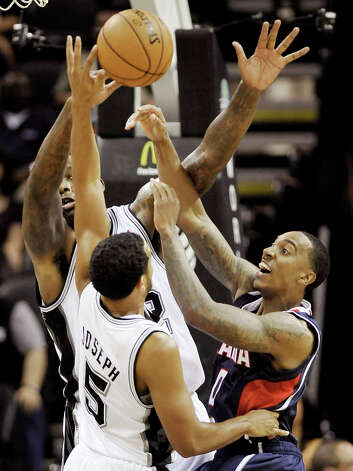 The Atlanta Hawks' Jeff Teague (right) is defended by the Spurs' Cory Joseph (5) and Eddy Curry during the first half Wednesday, Oct. 10, 2012, in San Antonio. Photo: Darren Abate, Associated Press / FR115 AP