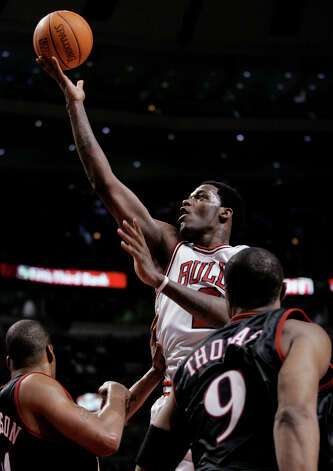 The Chicago Bulls' Eddy Curry (center) shoots over the Philadelphia 76ers' Corliss Williamson (left) and Kenny Thomas during the third quarter, Wednesday, Jan. 12, 2005, in Chicago. The Bulls won 110-78. (Brian Kersey / Associated Press) Photo: BRIAN KERSEY, AP / AP