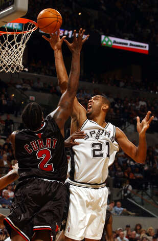 The Spurs' Tim Duncan goes over the Chicago Bulls' Eddy Curry during the first half at the SBC Center on Wednesday, Nov. 26, 2003. Photo: JERRY LARA, SAN ANTONIO EXPRESS-NEWS / SAN ANTONIO EXPRESS-NEWS