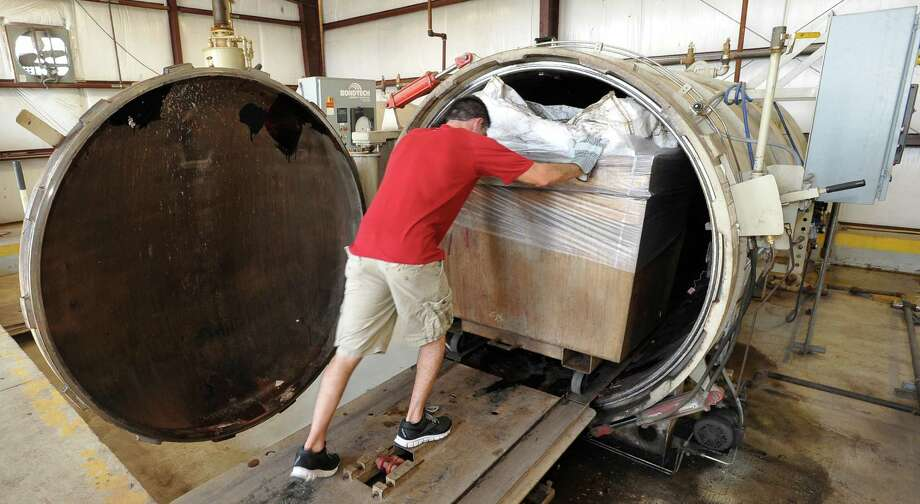 Jarred Raggio, an employee of BioMedical Waste Solutions in Port Arthur, pushes a full steel container containing ship waste into the hot,  open an autoclave that had just finished another sterilization process using 220 degree steam. The autoclave sterilizes medical waste and ship waste before it goes on to the Port Arthur landfill.  The nine cadaver ankles found in the Port Arthur landfill in September, went through one of these autoclaves accidently after arriving in a shipment. Dave Ryan/The Enterprise