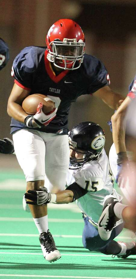 Alief Taylor's Chris Hardeman runs as he is tackled by Nimitz's Ricardo Ramierez (15) during the second half of the Nimitz High school football game played against Alief Taylor at Crump Stadium, Thursday, Oct. 11, 2012, in Houston. Alief Taylor won the game 28-7. Photo: Karen Warren, Houston Chronicle / © 2012  Houston Chronicle