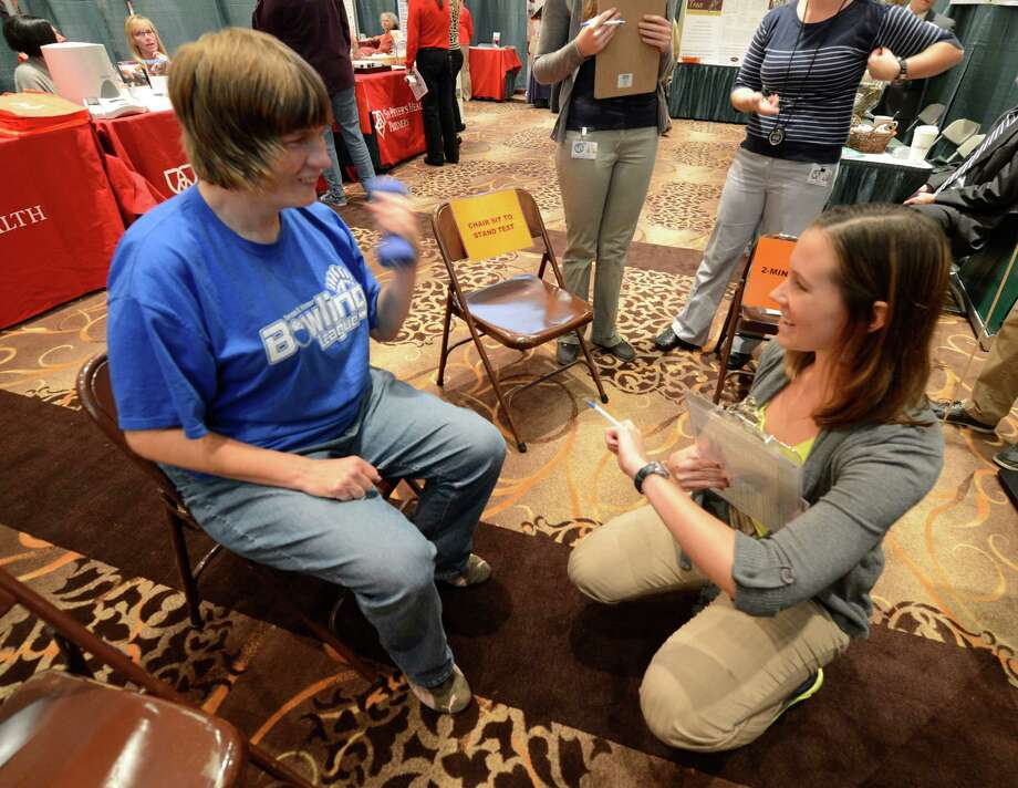 Kim Meyer, left performs an arm curl test for Physical Therapy student Jill Harter during a Senior Expo at the Clifton Park Center Mall in Clifton Park, N.Y. Oct. 11, 2012.     (Skip Dickstein/Times Union) Photo: Skip Dickstein / 00019317A