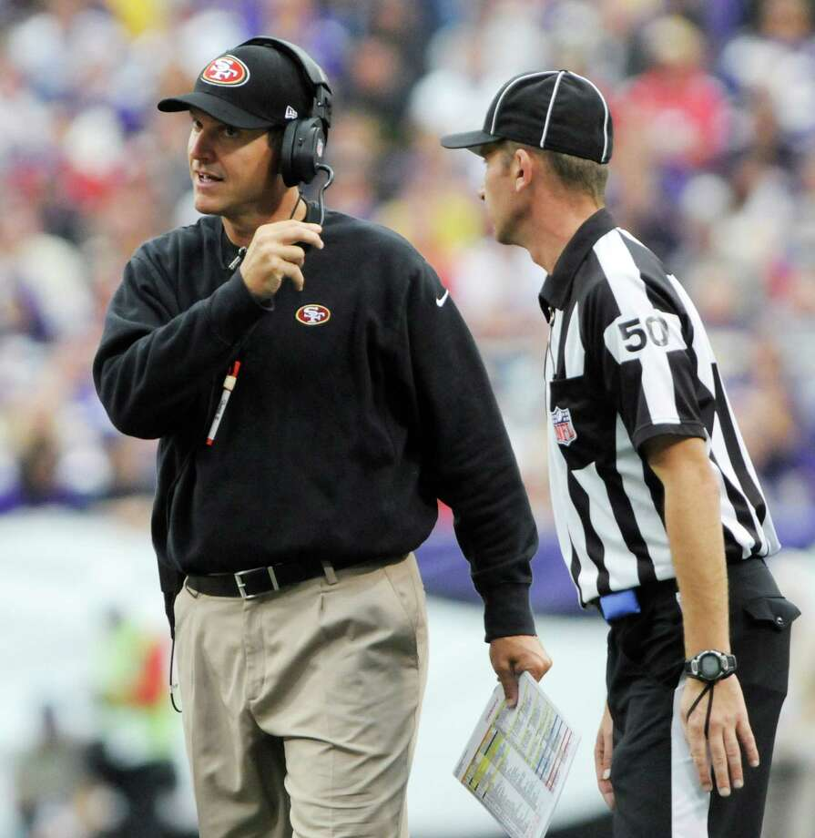 San Francisco 49ers head coach Jim Harbaugh, left, listens to replacement line judge Eric Hoffman during the second half of an NFL football game against the Minnesota Vikings Sunday, Sept. 23, 2012, in Minneapolis. Photo: Jim Mone, Associated Press / AP
