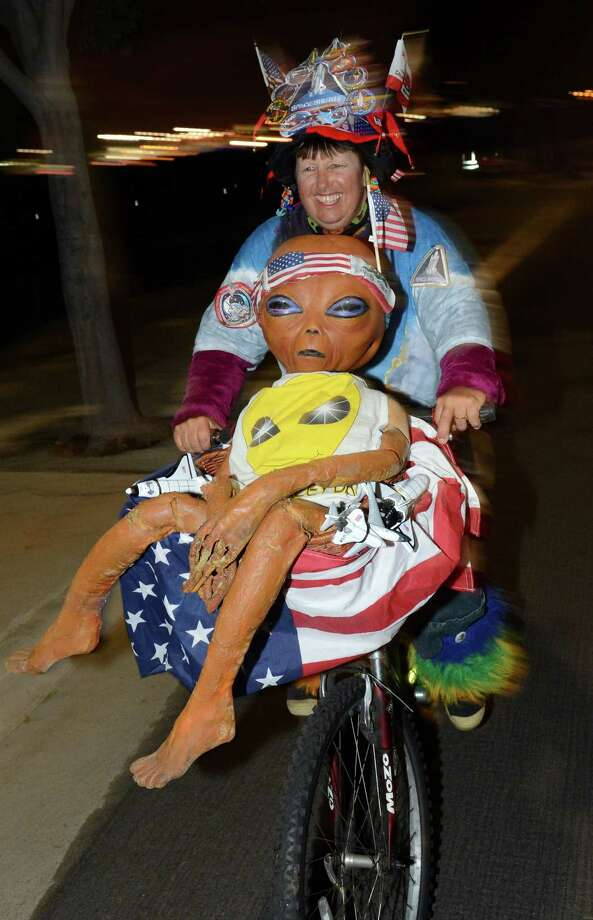 Space shuttle fan Vivian Robinson rides her bicycle covered in shuttle memorabilia, American flags and a alien doll,outside Los Angeles International Airport (LAX) as she waits to see Space Shuttle Endeavour, in the early morning hours October 12, 2012 in Los Angeles, California.  The Space Shuttle began its journey from LAX to its permenant home in Los Angeles, in the early morning hours Oct 12, 2012. Over the next two days, the 170,000-pound (77,272 kg) shuttle will travel at no more than 2 mph (3.2 km per hour) along a 12-mile (19km) route from LAX to it's final home at the California Science Center. NASA Space Shuttle Program ended in 2011 after 30 years and 135 missions. AFP PHOTO / Robyn BeckROBYN BECK/AFP/GettyImages Photo: ROBYN BECK, AFP/Getty Images / AFP