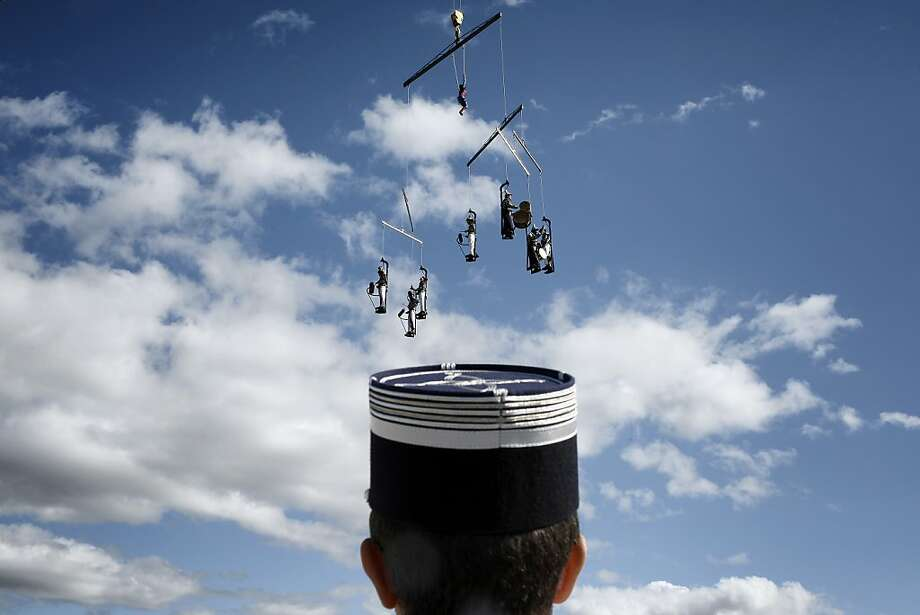 Suspended like a mobile over a gendarme's head are acrobatic street artists putting on musical performance in touristy Vallon-Pont-d'Arc, France. Photo: Jeff Pachoud, AFP/Getty Images