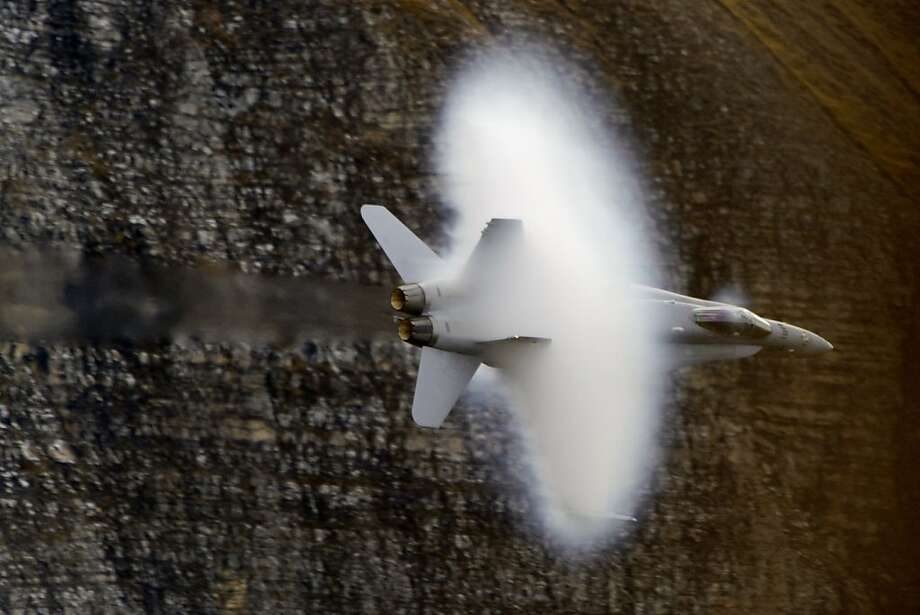 Switzerland's fleet week:A vapor cone forms around an F/A-18 Hornet during  maneuvers over Axalp in the Bernese Oberland. Photo: Fabrice Coffrini, AFP/Getty Images