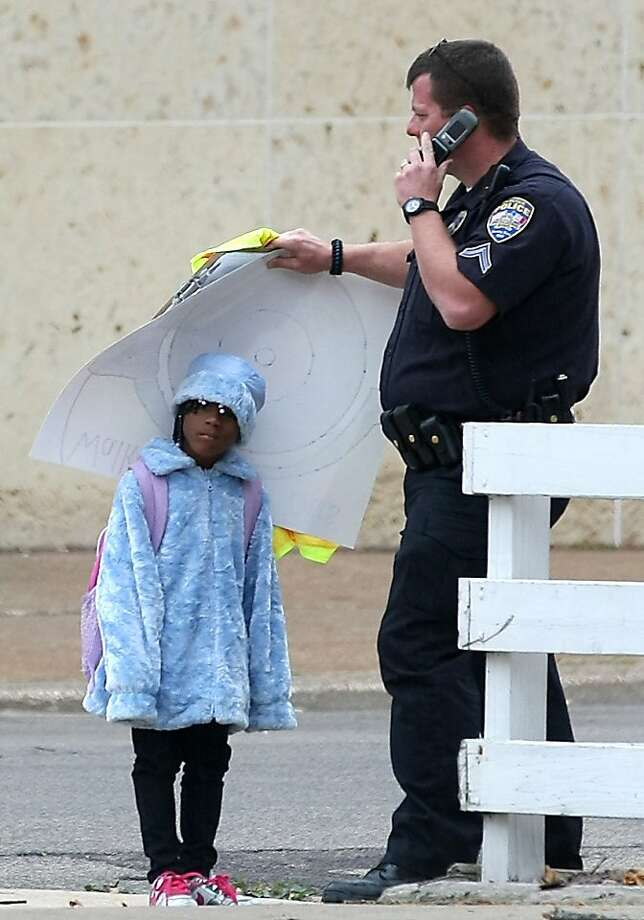 All in the line of duty: in Dubuque, Iowa, police Cpl. Nathan Tyler shields first-grader Samaya Curtis from the rain with a poster. Photo: Jessica Reilly, Associated Press