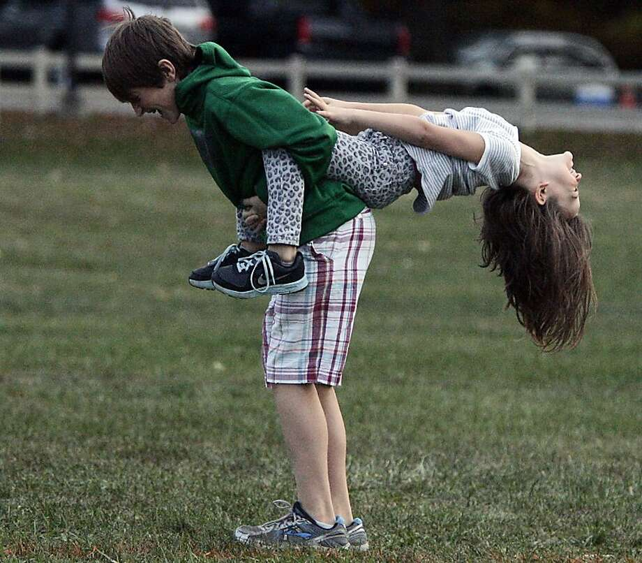 Brothers were made for riding:Theran Coulopoulos gives his little sister, Angela, a piggyback ride at Sunset Hill Farm County Park in Valparaiso, Ind. Photo: Bob Wellinski, Associated Press