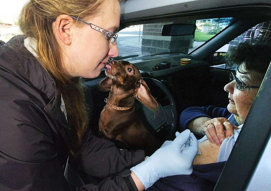 One good turn deserves a wet face: Louie thanks nurse Aimee Faulkner for giving his human, Audrey Hann, a flu shot at a free, drive-through vaccination clinic in Soldotna, Alaska. Photo: M. Scott Moon, Associated Press