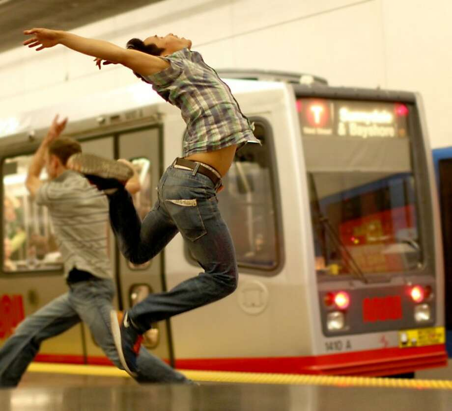 Nitpat Pholchai and Tim Boxell show off their moves at a Muni station. Photo: Afshin Odabaee