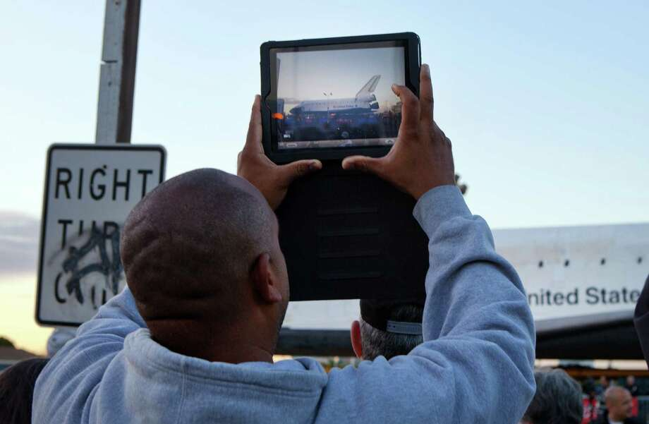 A member of the crowd takes a photo of the space shuttle Endeavour as it begins its trip from Los Angeles International Airport to the California Science Center, in Los Angeles, Oct. 12, 2012. Endeavour will be towed 12 miles through the dense urban landscape of Los Angeles, past streetlights and trees, on its way to retirement at the science center. (Monica Almeida/The New York Times) Photo: MONICA ALMEIDA, NYT / NYTNS