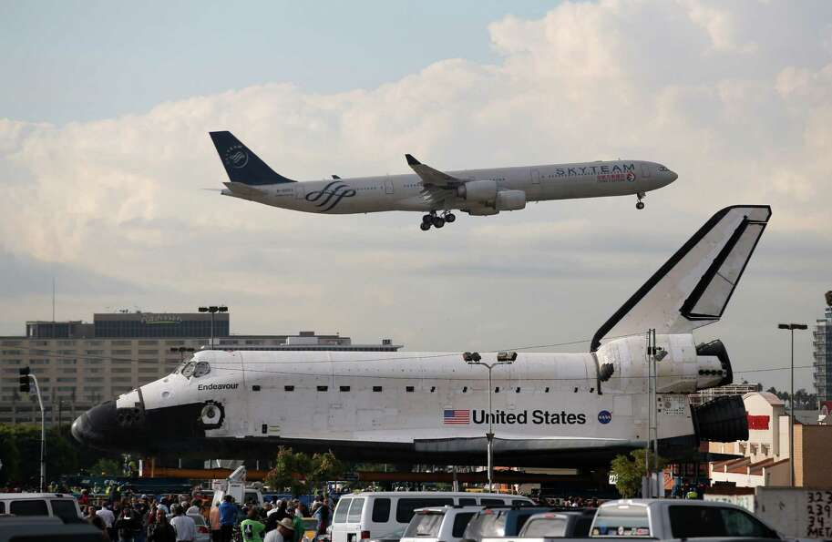 A China Eastern Airlines jet flies near the space shuttle Endeavour in Los Angeles, Friday, Oct. 12,