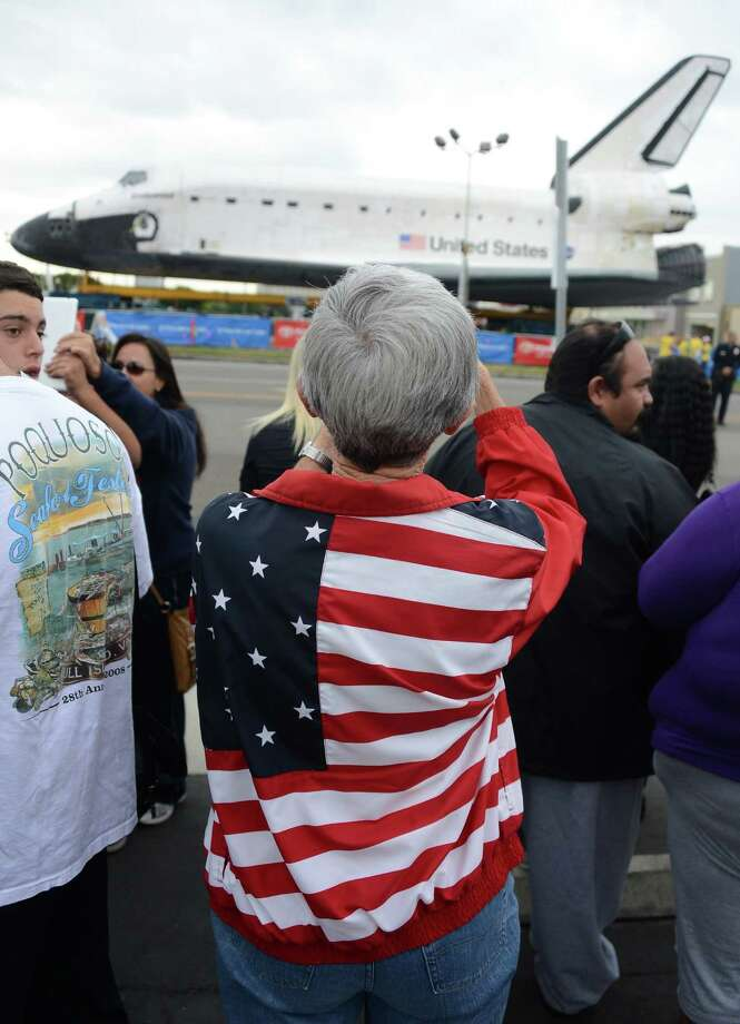 Spectators come to watch the Space Shuttle Endeavour as it rests during its first temporary stop at Westchester square during its final ground journey in Los Angeles, California on October 12, 2012. Over the next two days, the 170,000-pound (77,272 kg) shuttle will travel at no more than 2 mph (3.2 km per hour) along a 12-mile (19km) route from Los Angeles International Airport to its final home at the California Science Center. NASA's Space Shuttle Program ended in 2011 after 30 years and 135 missions. AFP PHOTO/JOE KLAMARJOE KLAMAR/AFP/GettyImages Photo: JOE KLAMAR, AFP/Getty Images / AFP