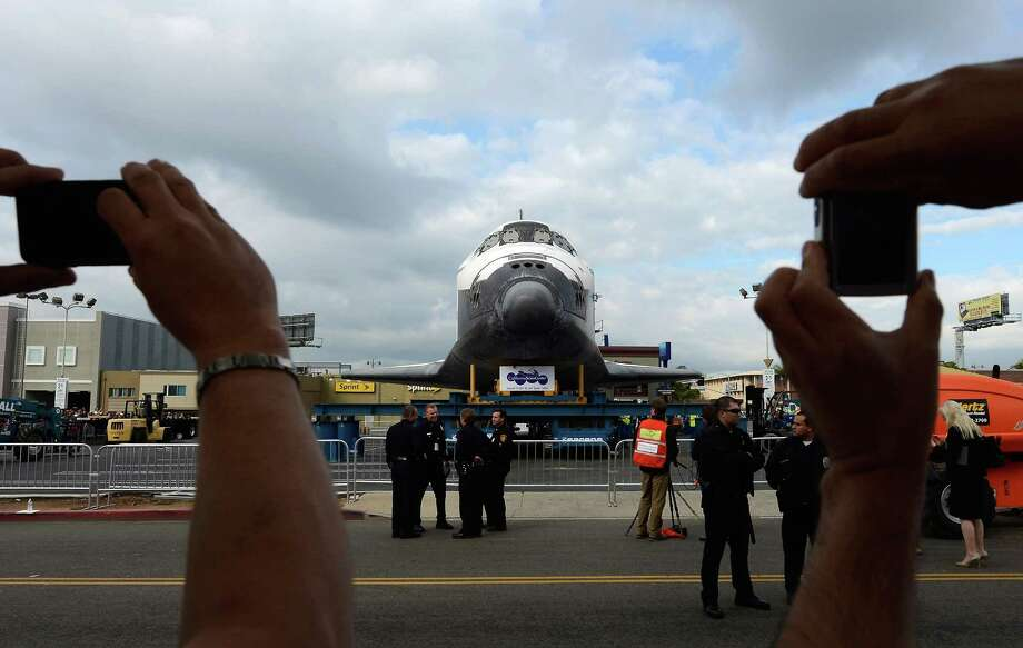 Spectators take pictures of the space shuttle Endeavour parked in a mall parking lot on October 12, 2012 in Los Angeles, California.  The space shuttle Endeavour is making the journey from Los Angeles International Airport to the California Science Center to go on permanent public display. Endeavour was transported cross-country atop NASA's Shuttle Carrier Aircraft from Kennedy Space Center in Florida to LAX during its last flight ever on September 21. Photo: Kevork Djansezian, Getty Images / 2012 Getty Images