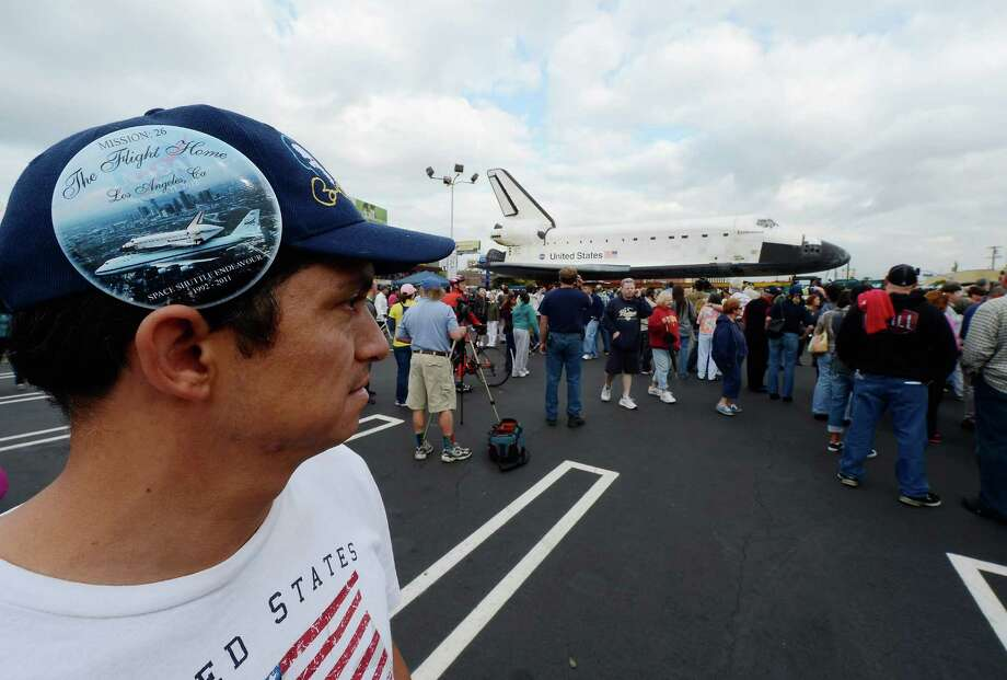 A Los Angeles resident wearing a large button showing space shuttle Endeavour flying over downtown Los Angeles gets up close to the orbiter parked in a mall parking lot on October 12, 2012 in Los Angeles, California.  The space shuttle Endeavour is making the journey from Los Angeles International Airport to the California Science Center to go on permanent public display. Endeavour was transported cross-country atop NASA's Shuttle Carrier Aircraft from Kennedy Space Center in Florida to LAX during its last flight ever on September 21. Photo: Kevork Djansezian, Getty Images / 2012 Getty Images