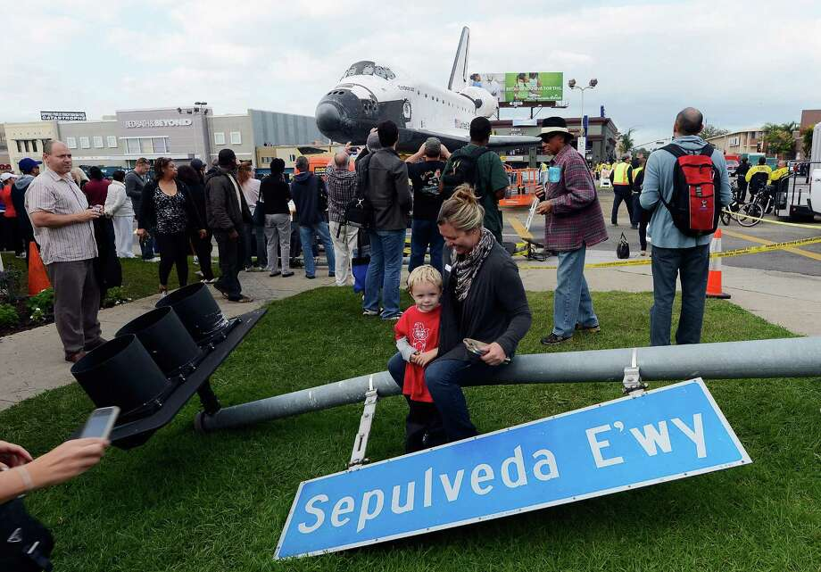 One of hundreds of street signs temporarily removed for the 12-mile road trip of space shuttle Endeavour is used as prop as a family gets their picture taken with the orbiter parked in a mall parking lot on October 12, 2012 in Los Angeles, California.  The space shuttle Endeavour is making the journey from Los Angeles International Airport to the California Science Center to go on permanent public display. Endeavour was transported cross-country atop NASA's Shuttle Carrier Aircraft from Kennedy Space Center in Florida to LAX during its last flight ever on September 21. Photo: Kevork Djansezian, Getty Images / 2012 Getty Images