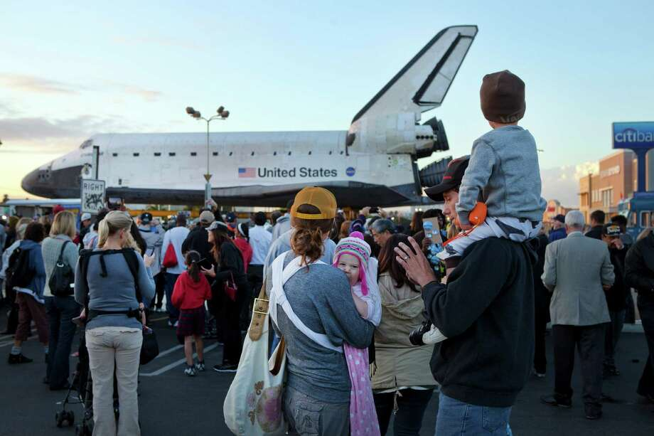 A crowd gathers to watch the space shuttle Endeavour begin its trip from Los Angeles International Airport to the California Science Center, in Los Angeles, Oct. 12, 2012. Endeavour will be towed 12 miles through the dense urban landscape of Los Angeles, past streetlights and trees, on its way to retirement at the science center. Photo: MONICA ALMEIDA, New York Times / NYTNS