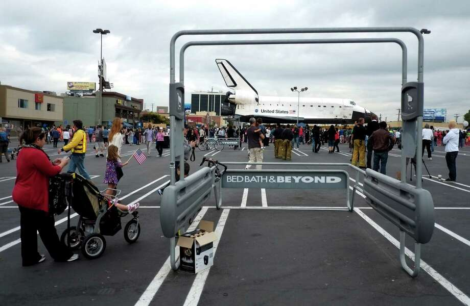 "The space shuttle Endeavour sits in a strip mall in Los Angeles, Friday, Oct. 12, 2012. Endeavour's two-day, 12-mile (19 kilometer) road trip to the California Science Center where it will be put on display kicked off around midnight Friday. Rolled on a 160-wheeled carrier, it left from a hangar at the Los Angeles International Airport, passing diamond-shaped ""Shuttle Xing"" signs, and reached city streets about two hours later. (AP Photo/Jae C. Hong) Photo: Jae C. Hong, Associated Press / AP"
