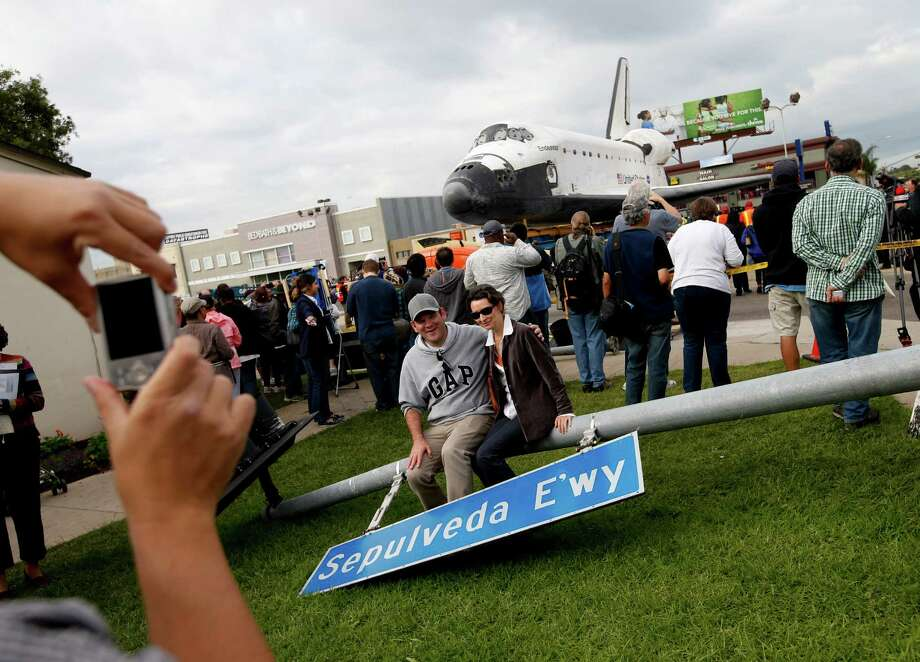 A couple poses with a street sign temporarily removed prior to the transfer of the space shuttle Endeavour in Los Angeles, Friday, Oct. 12, 2012. Endeavour's 12-mile road trip kicked off shortly before midnight Thursday as it moved from its Los Angeles International Airport hangar en route to the California Science Center, its ultimate destination, said Benjamin Scheier of the center. (AP Photo/Jae C. Hong) Photo: Jae C. Hong, Associated Press / AP