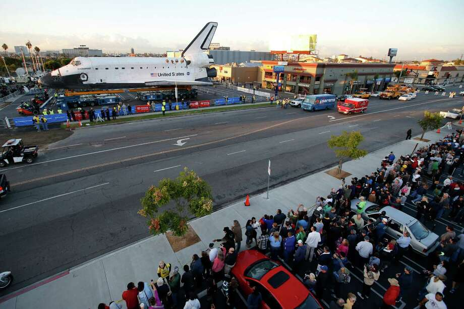 Spectators gather to watch the space shuttle Endeavour in Los Angeles, Friday, Oct. 12, 2012. Endeavour's 12-mile road trip kicked off shortly before midnight Thursday as it moved from its Los Angeles International Airport hangar en route to the California Science Center, its ultimate destination, said Benjamin Scheier of the center. (AP Photo/Jae C. Hong) Photo: Jae C. Hong, Associated Press / AP