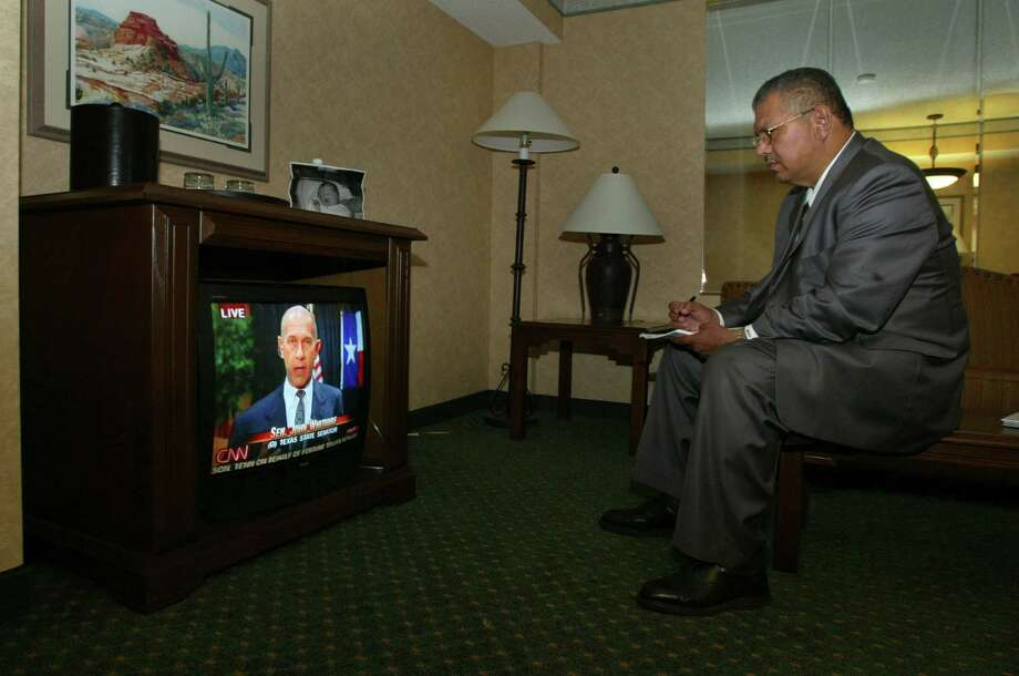 State Sen. Mario Gallegos, D-Houston, watches television in his hotel room in Albuquerque, N.M. in 2003. Seen on the TV is a live interview with Sen. John Whitmire, also a runaway Houston Democrat. Photo: D. Fahleson, Houston Chronicle / Houston Chronicle