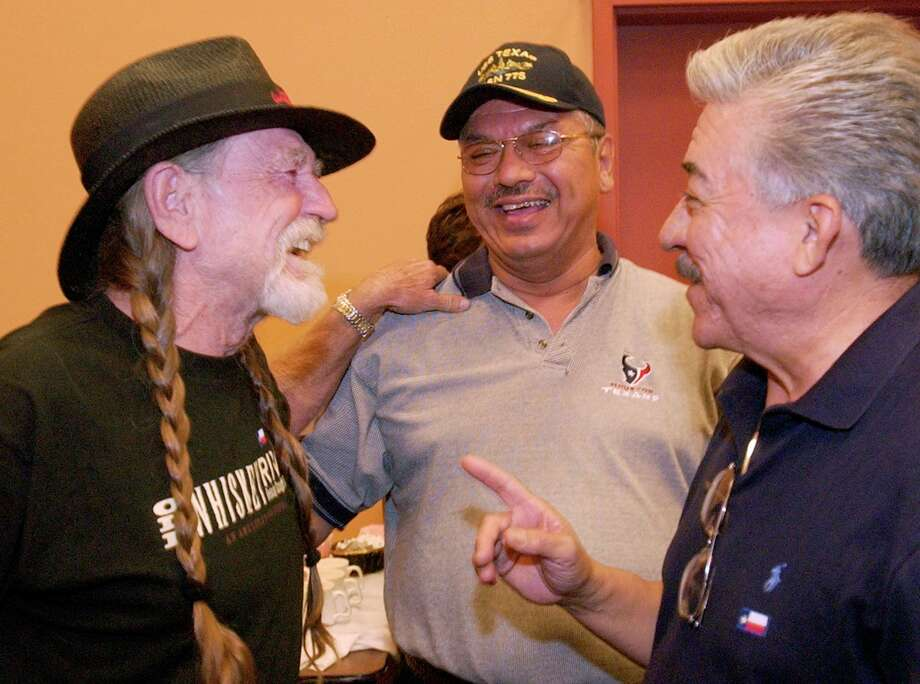 Texas musician Willie Nelson visits with Democratic state Sens. Mario Gallegos, center, and  Gonzalo Barrientos backstage at an Albuquerque, N.M., concert in 2003. Photo: JAKE SCHOELLKOPF, AP / AP