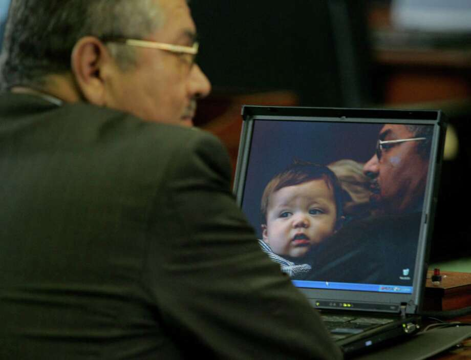 State Sen. Mario Gallegos, Jr., left, sits at his computer with a screen saver with himself and his 17-month-old grandson Jake Gallegos during Wednesday's Senate session in the Texas Senate Chamber in the Texas State Capital in Austin, Jan. 12, 2005.  Photo: JAMES NIELSEN, HOUSTON CHRONICLE / HOUSTON CHRONICLE