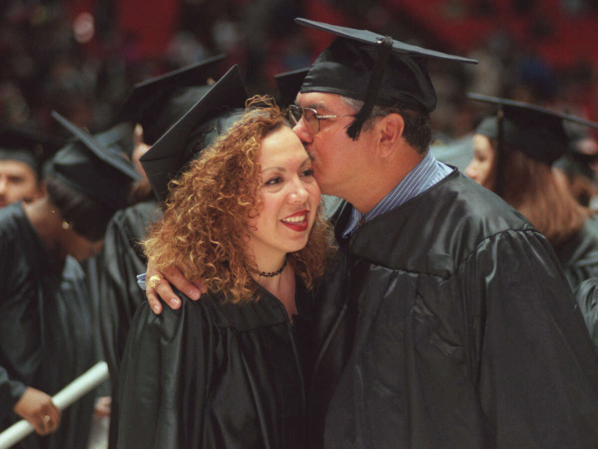 State Sen. Mario Gallegos and his daughter, Ali, embrace Saturday in Hofheinz Pavilion after they both received bachelor's degrees from the University of Houston-Downtown, 1999.