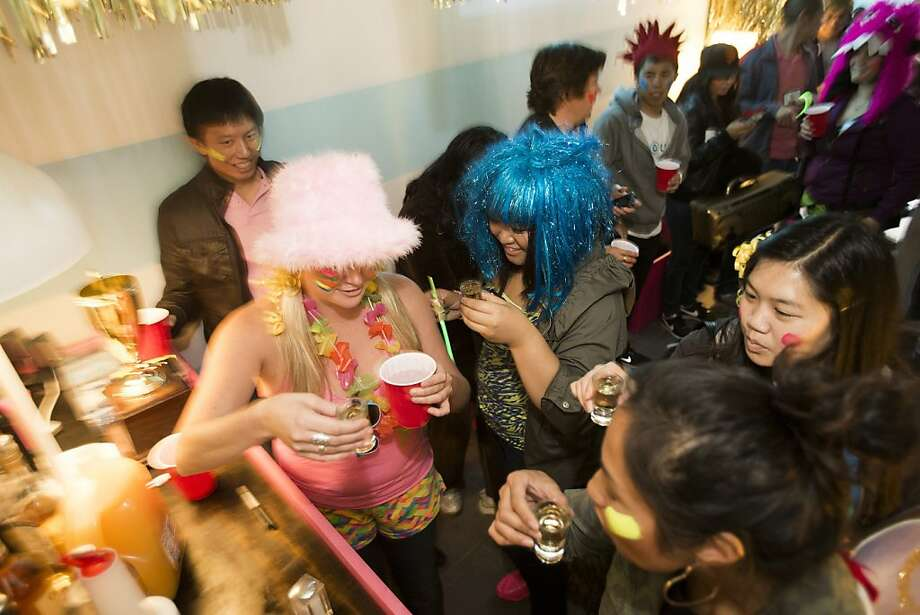 Carrie Tucker (in pink hat) and Sheena Thach (blue wig) warm up for a California League of Adult Scavenger Hunters event with a Tequila shot. Photo: Stephen Lam, Special To The Chronicle
