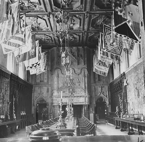 The refectory, or dining room, which was the artistic pride of William Randolph Hearst. Silken Sienese patio banners hang between the high windows. The ceiling is from an Italian monastery. The floors are marble. Red brocaded Savonarola chairs are a highlight. Photo was taken June 1, 1958.