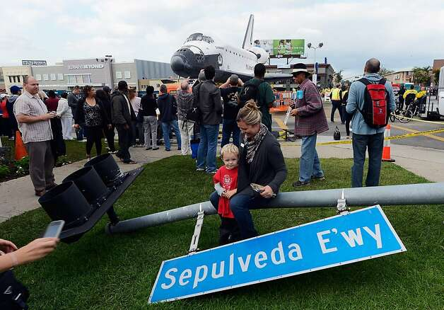 A street sign temporarily removed for the Endeavour's two-day, 12-mile trip is a convenient perch for a family snapshot with the space shuttle sitting in a mall parking lot in Los Angeles. Photo: Kevork Djansezian, Getty Images
