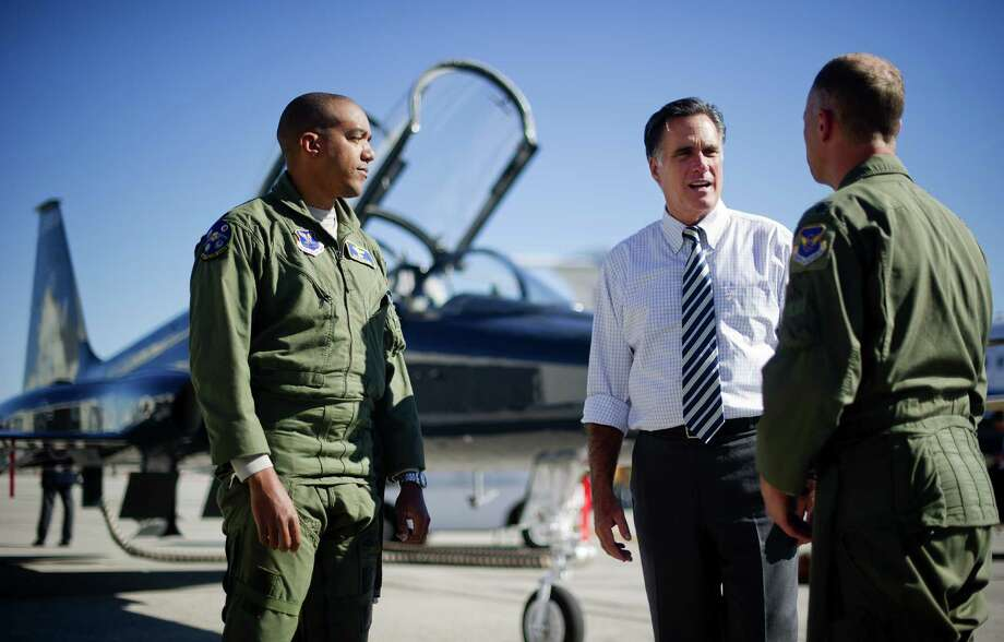 "GOP presidential nominee Mitt Romney talks with two Air Force pilots Friday  at Port Columbus International Airport in Ohio. Romney accused President Barack Obama of ""doubling down on denial""  iver the Benghazi attack. Photo: JIM WATSON / AFP"