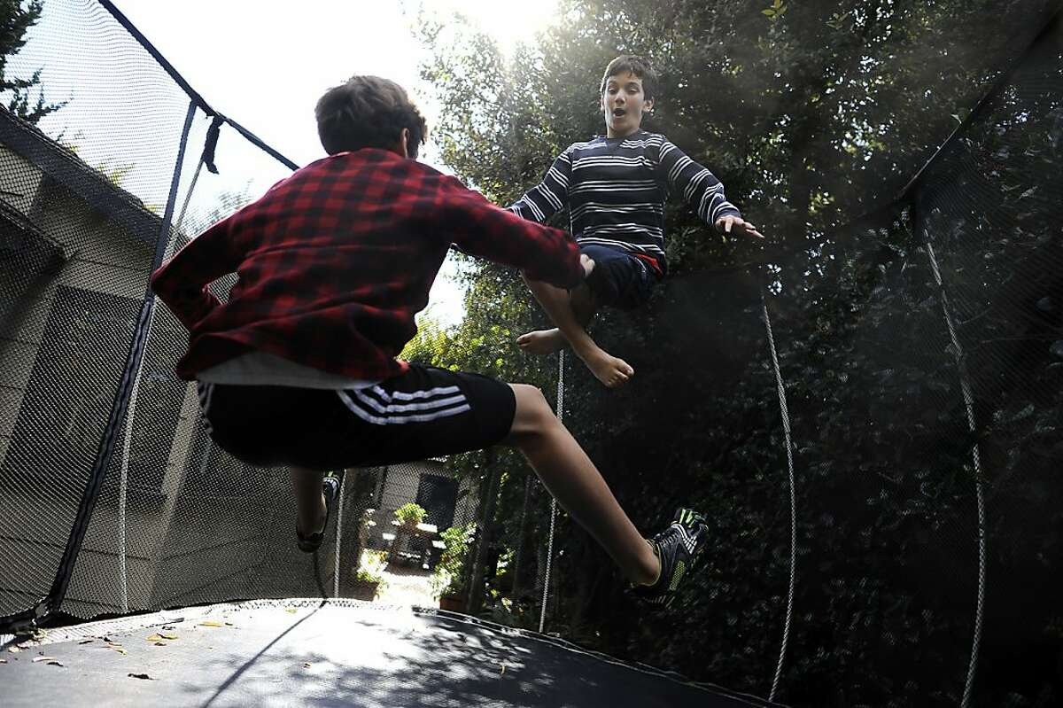 Colman Chadmon (right) jumps on the trampoline with his brother Aidan in their back yard at their home in Palo Alto on Tuesday, October 10th, 2012. Colman has been asked to leave his middle school in Palo Alto, Calif. because he has the genetic markers for cystic fibrosis and the school doesn't want him near another student who is already there with CF.