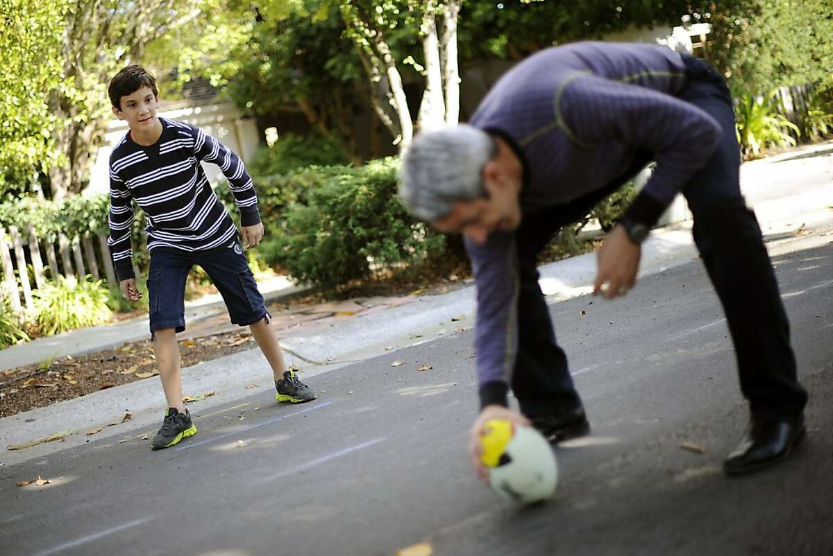 Colman Chadmon (L) plays football with his dad, Jaimy Chadmon, and his brother Aidan in front of their home on Tuesday, October 10th, 2012. Colman has been asked to leave his middle school in Palo Alto, CA because he has the genetic markers for cystic fibrosis and the school doesn't want him near another student who is already there with CF.