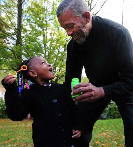 Glover Gardner plays outside with his three-year-old granddaughter, Kami Gardner, after school Friday, Oct. 12, 2012 at his home in Bridgeport, Conn. Photo: Autumn Driscoll / Connecticut Post