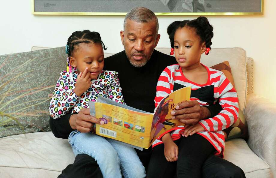 Glover Gardner reads to his granddaughters, Kami Gardner, 3, left, and Poet Gardner, 4, after school Friday, Oct. 12, 2012 at his home in Bridgeport, Conn. Photo: Autumn Driscoll / Connecticut Post