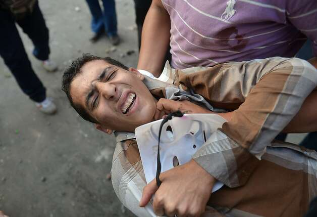 TOPSHOTS Egyptians evacuate a wounded man during clashes between government supporters and opponent of the Muslim Brotherhood and President Mohamed Morsi in Tahrir square in Cairo on October 12, 2012, in the worst violence over Egypt's new Islamist leader, a day after he crossed swords with the judiciary. The health ministry said at least 12 people were wounded as protesters showered each other with stones, after Morsi supporters tore down a podium from which anti-Brotherhood chants were being orchestrated. TOPSHOTS/AFP PHOTO / KHALED DESOUKIKHALED DESOUKI/AFP/GettyImages Photo: Khaled Desouki, AFP/Getty Images