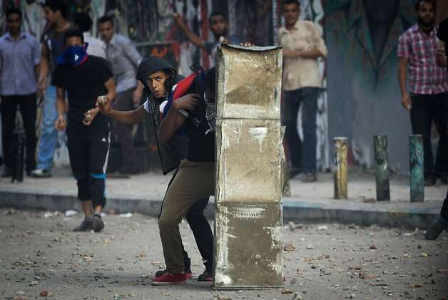 A protester throws a stone after scuffles broke out between groups of protesters in Tahrir square when chants against the new Islamist president angered some in the crowd in Cairo, Egypt, Friday, Oct. 12, 2012. Thousands of supporters and opponents of Egypt's new Islamist president clashed in Cairo's Tahrir Square on Friday, hurling stones and concrete and swinging sticks at each other in the first such violence since Mohammed Morsi took office more than three months ago.(AP Photo/Khalil Hamra) Photo: Khalil Hamra, Associated Press