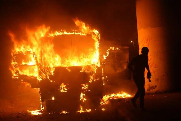 TOPSHOTS An Egyptian man walks past a burning bus during clashes between government supporters and opponents of the Muslim Brotherhood and President Mohamed Morsi in Tahrir square in Cairo on October 12, 2012, in the worst violence over Egypt's new Islamist leader, a day after he crossed swords with the judiciary. The health ministry said at least 12 people were wounded as protesters showered each other with stones, after Morsi supporters tore down a podium from which anti-Brotherhood chants were being orchestrated. TOPSHOTS/AFP PHOTO/STRSTR/AFP/GettyImages Photo: Str, AFP/Getty Images